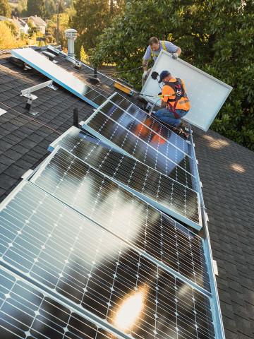 Handwerker installieren Solaranlage auf Hausdach