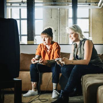 Frauen spielen mit Controllern und Abstand zum Bildschirm
