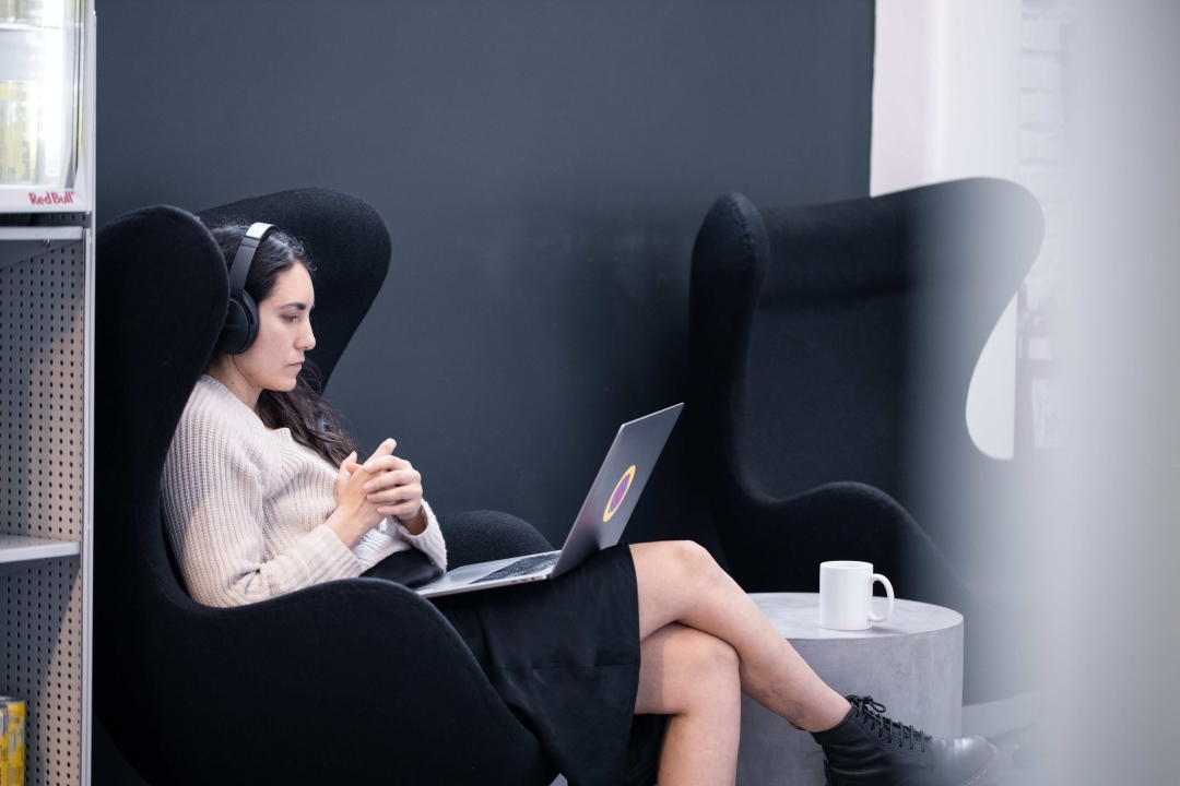 A photograph of a woman using her computer with headphones on