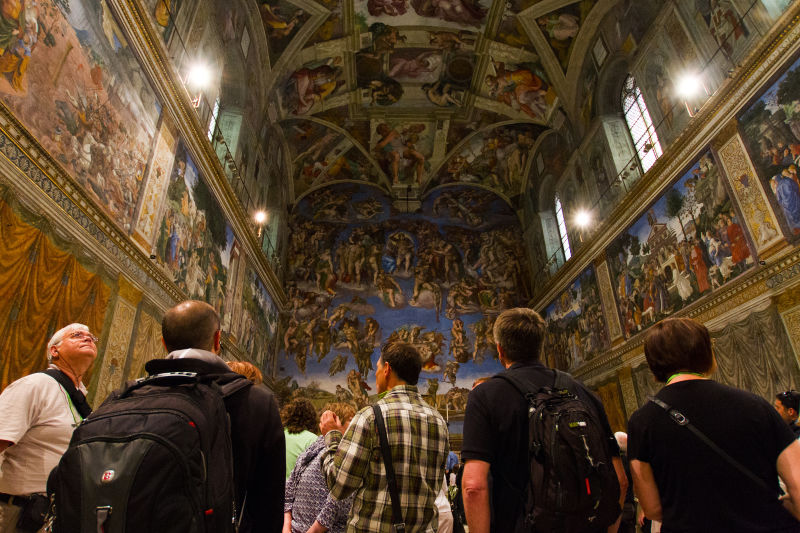Visitors look at the frescoes in the Sistine Chapel