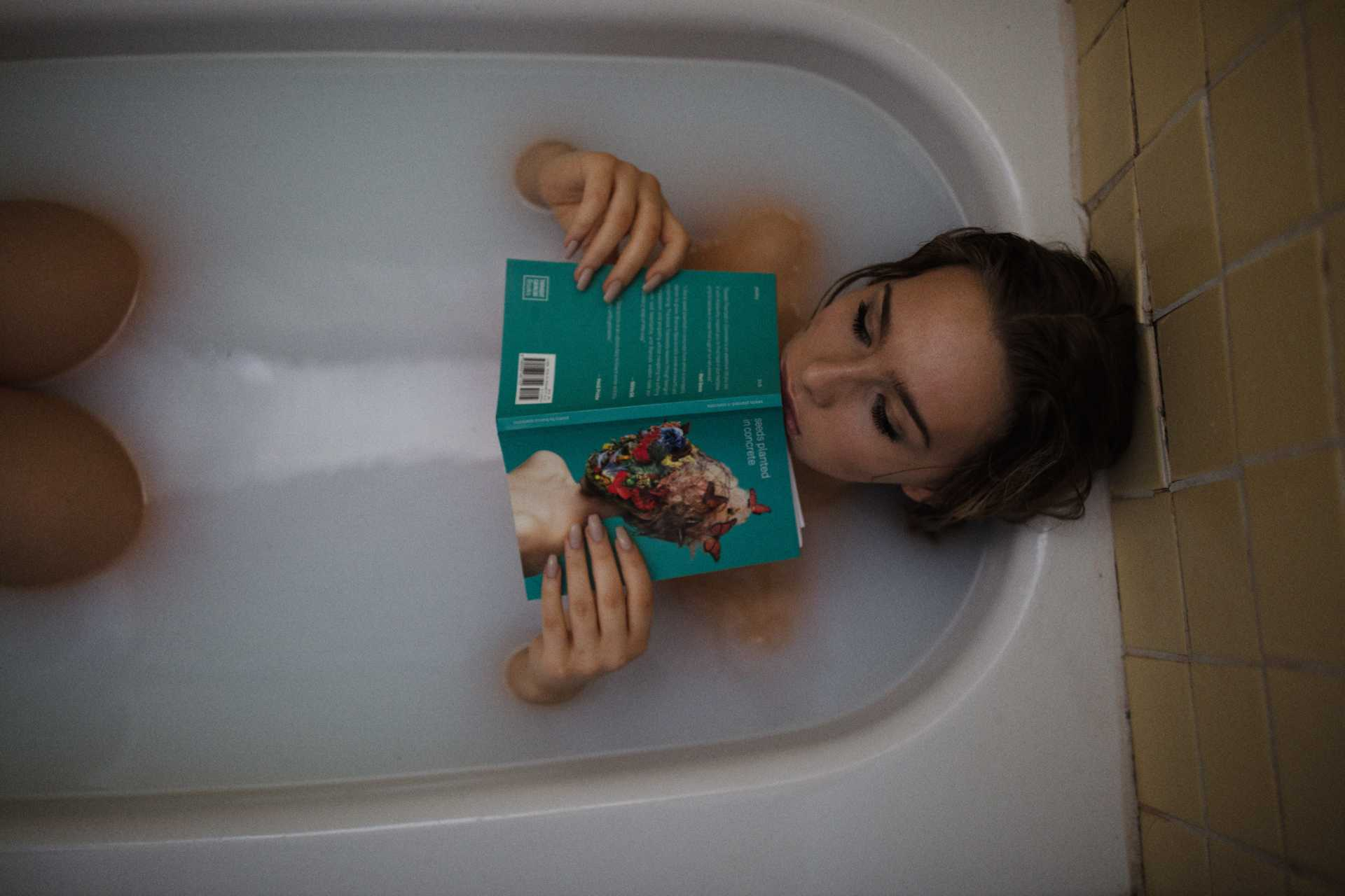 woman in tub with book, thinking about STI treatment
