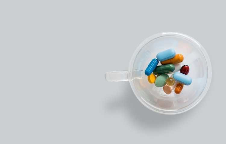 Tablets and capsules representing UTI treatment in a clear cup.