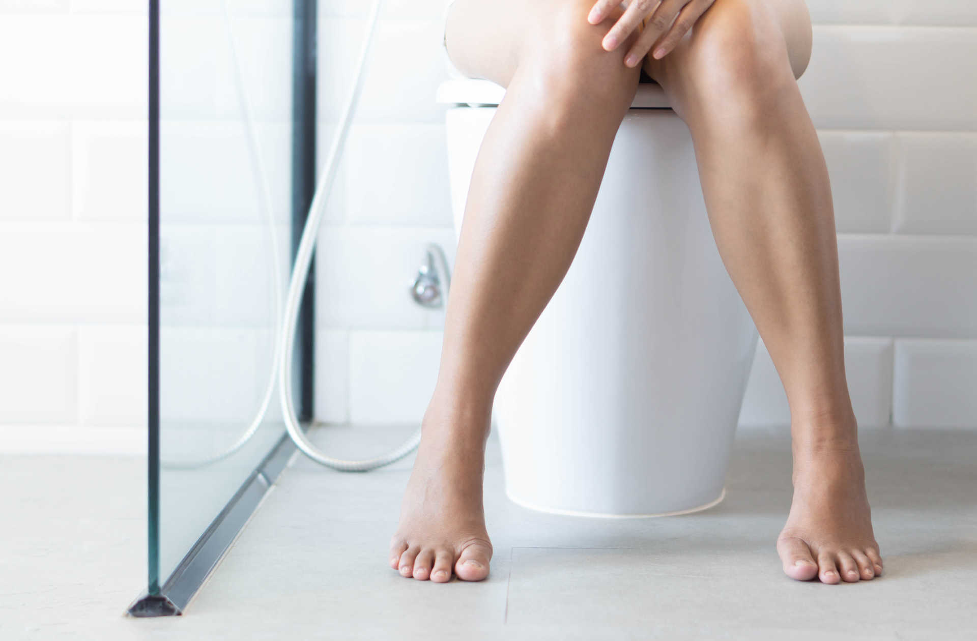 Woman with UTI on toilet