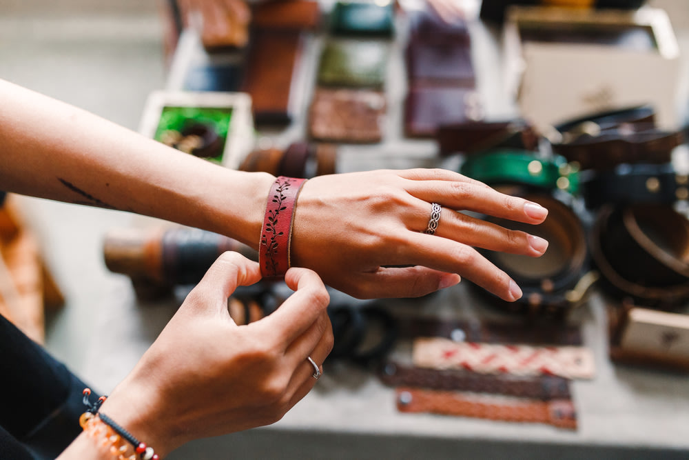 Woman choosing leather jewelry bracelets at the handmade craft market