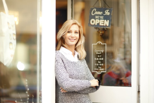 Portrait of designer woman standing in front of small vintage store. Small business