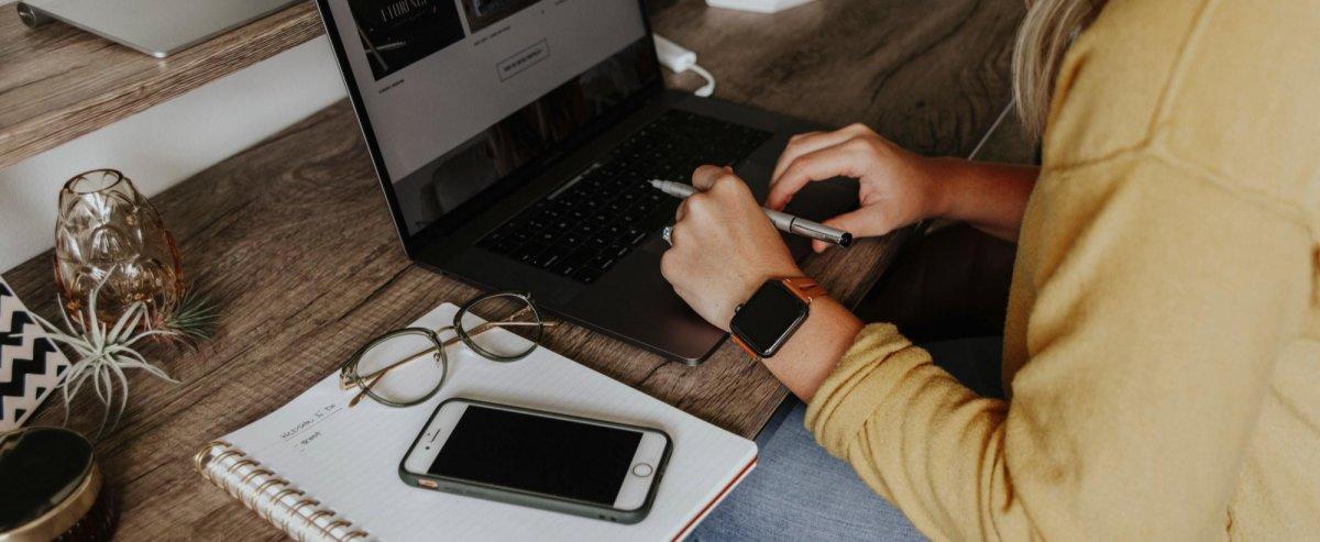 frau arbeitet am computer smartphone auf notizblock fuer buchhaltung
