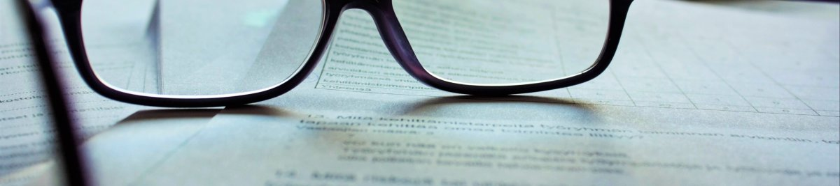 schwarze lesebrille auf einem stapel dokumente über das Kassengesetz 2020