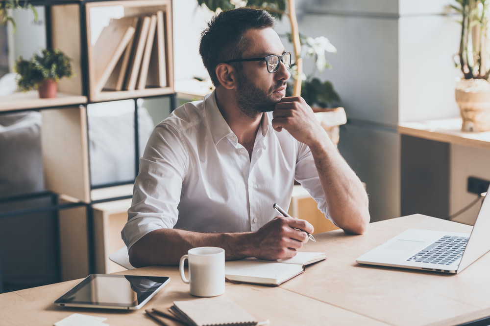 Thoughtful mature man holding pen and looking away while sitting at his working place in office