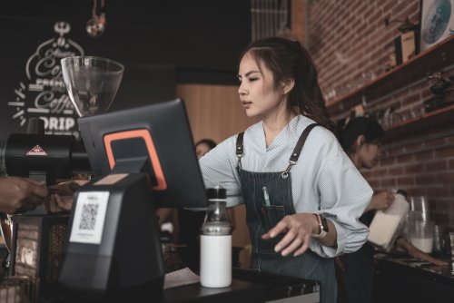 Cashier at cafe using POS system