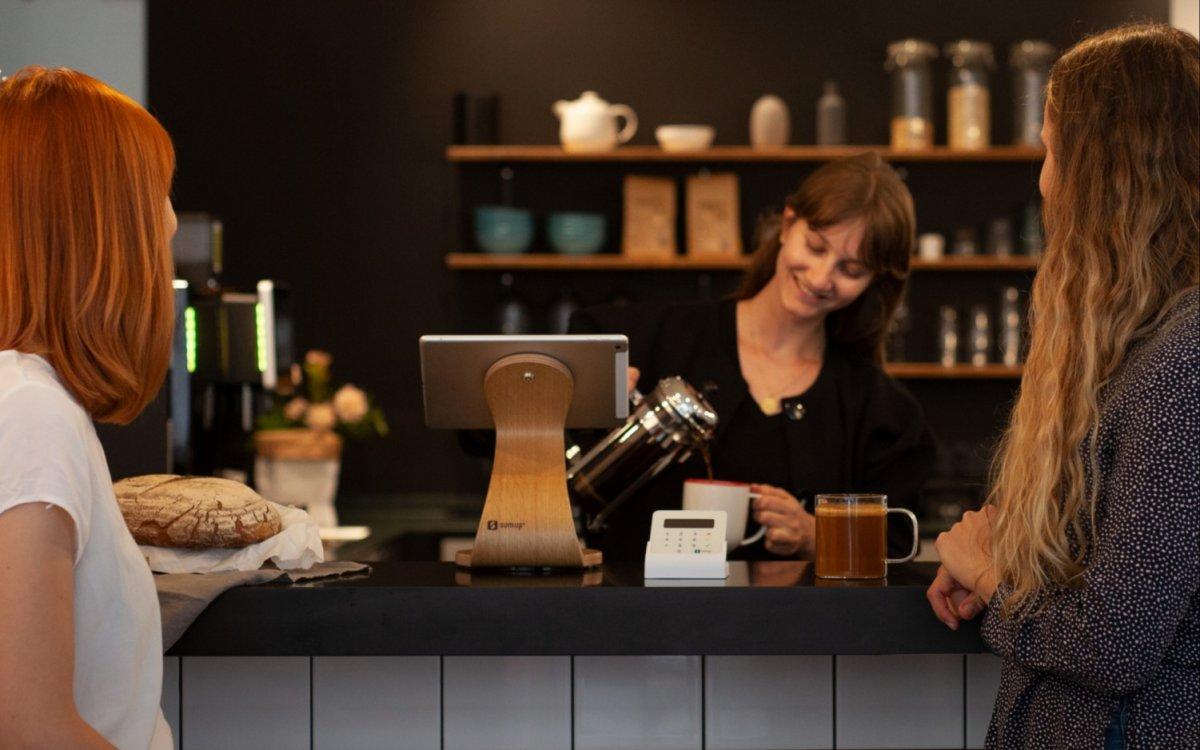 zwei personen werden an café theke bedient - mit dem sumup kassensystem
