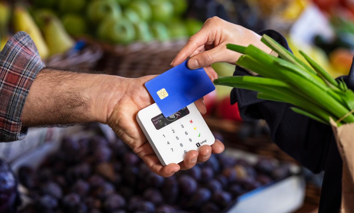 Kartenterminal in der Hand eines Gemüsehändlers