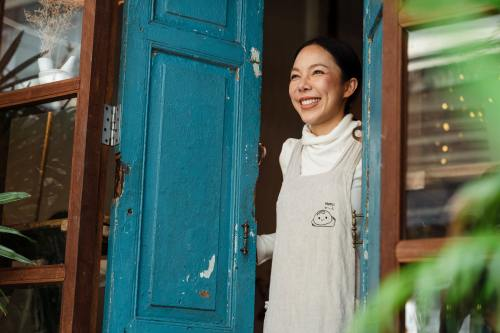 Happy coffee shop owner at entrance