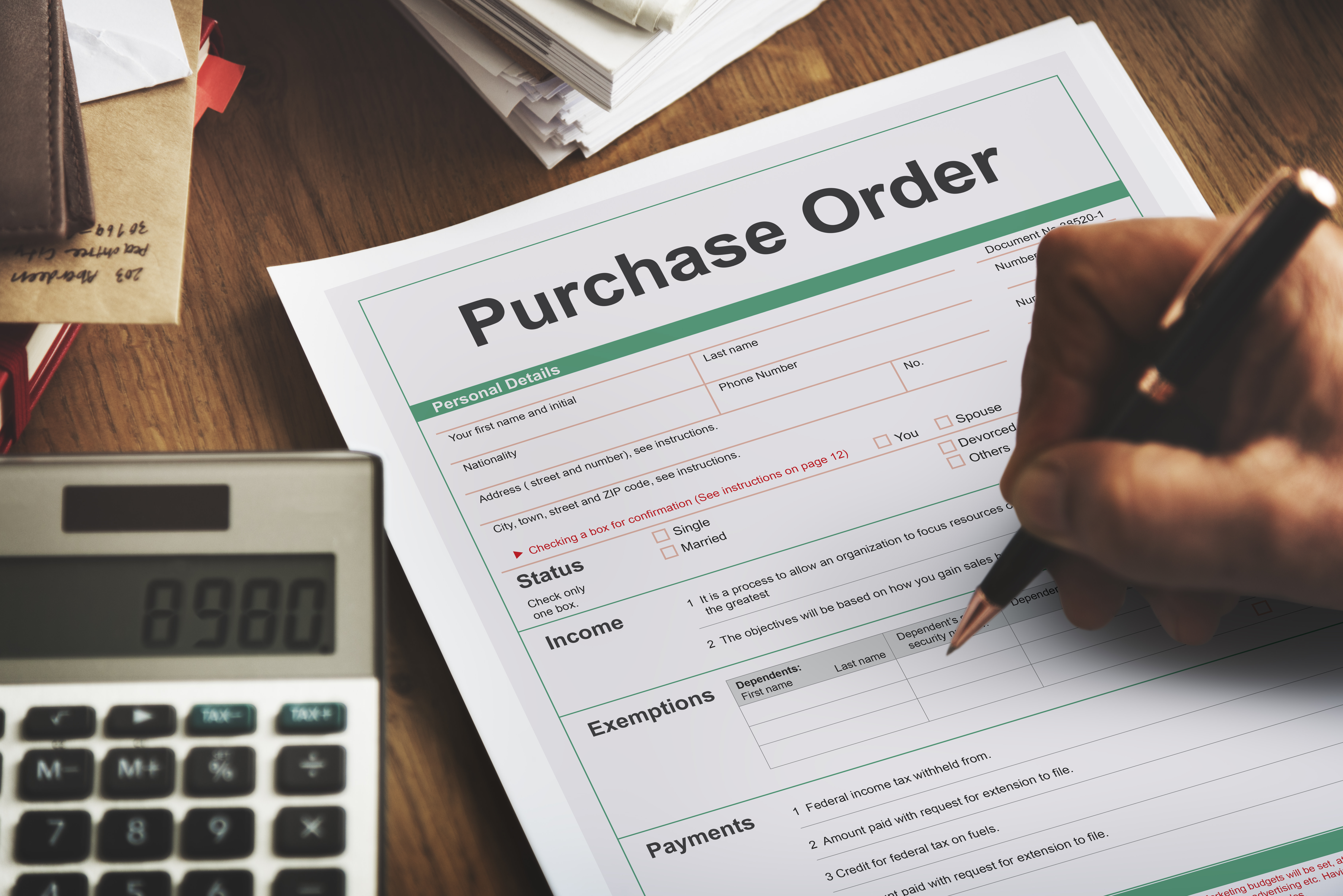 Purchase order on desk with person holding pen