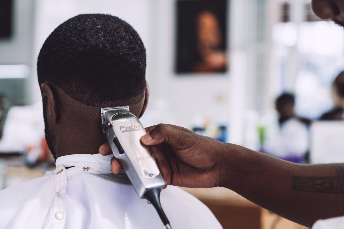 Men at barber is getting hair cut.