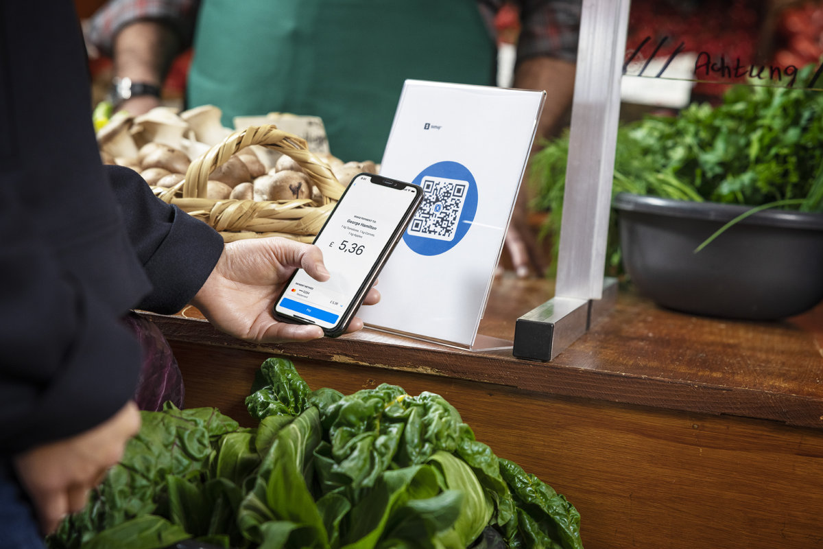 A customer holds their smartphone, about to complete a payment online after scanning a QR code display.