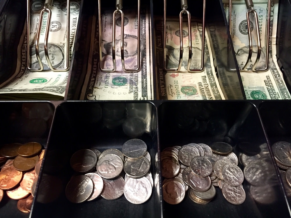 American dollar notes and coins inside the cash register machine