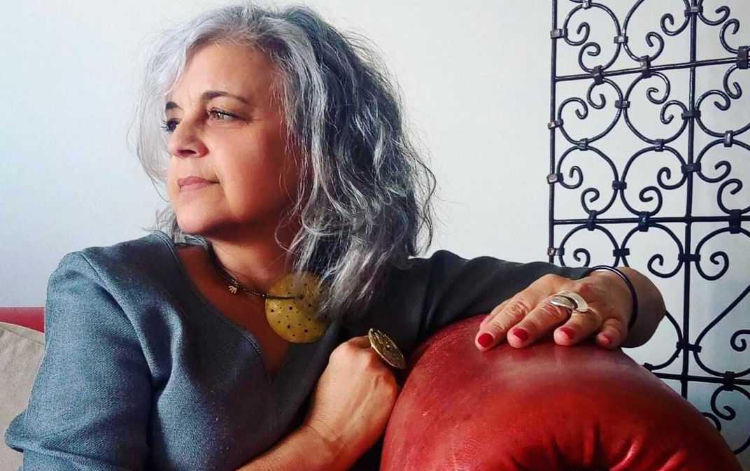 Una donna è seduta sul divano e indossa accessori che ha creato con le sue mani.