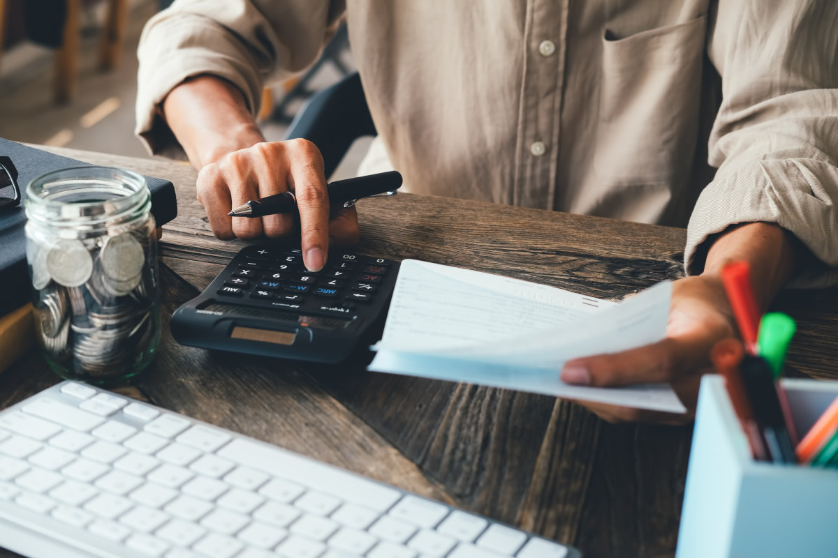 uomo fa la contabilità con calcolatrice penna e fogli