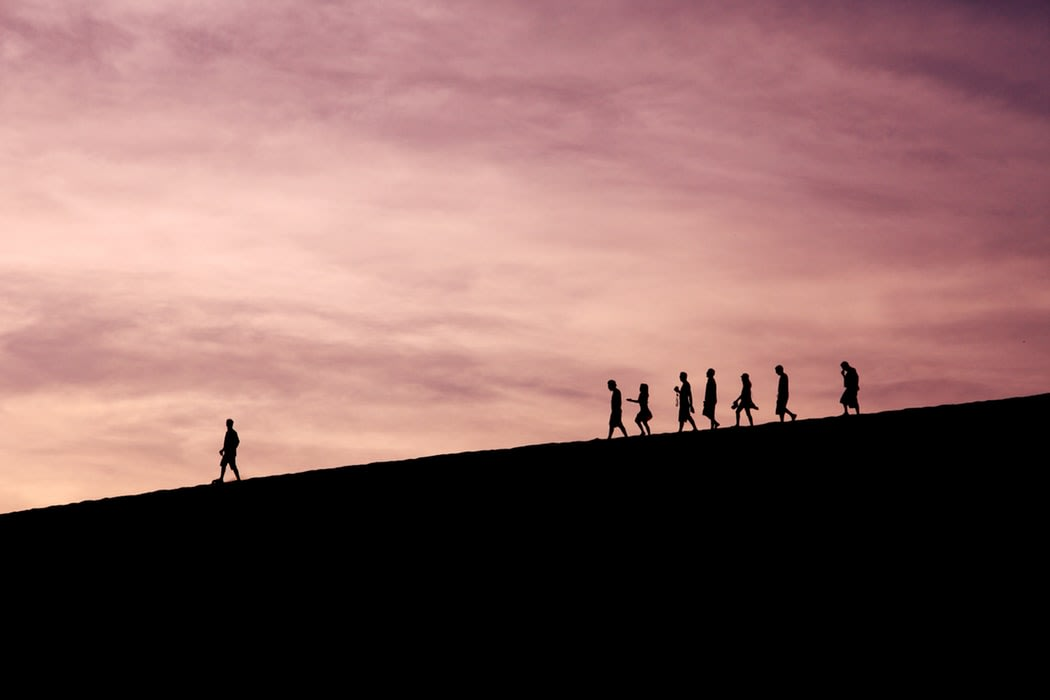 mountain sunset, one person is leading and being followed by a group