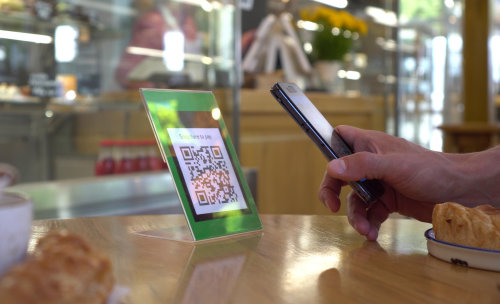 A customer uses their smartphone to scan a QR code at a table set with baked goods.