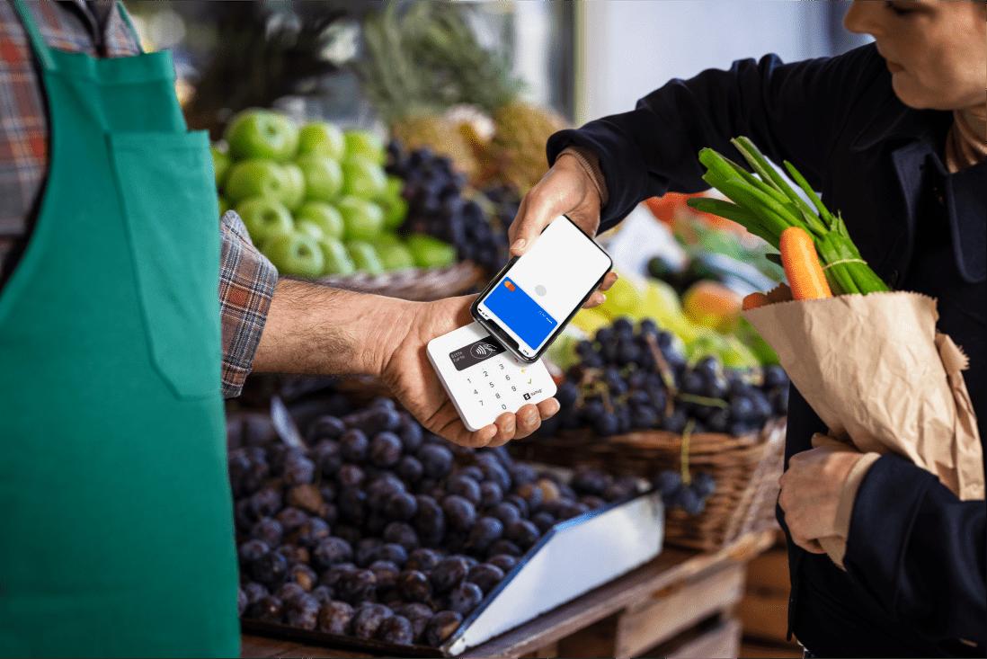 Kunde zahlt beim Gemüsehändler mit dem Handy