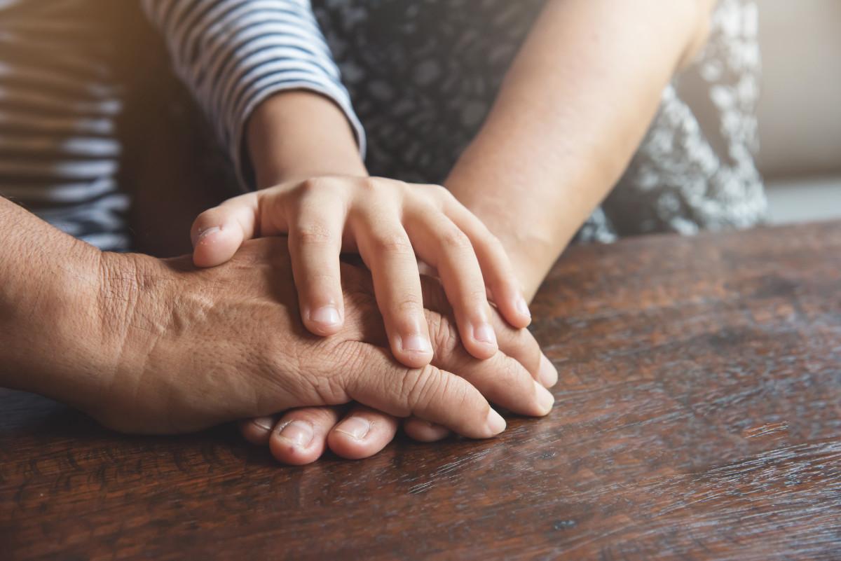 mani di una famiglia sul tavolo
