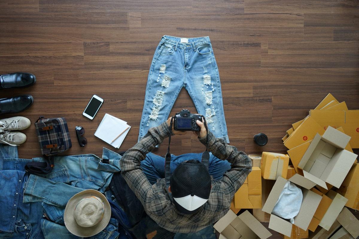 Un uomo seduto a terra scatta una foto di un paio di jeans con una macchina fotografica. I pantaloni sono circondati da altri capi di abbigliamento e imballi vuoti.