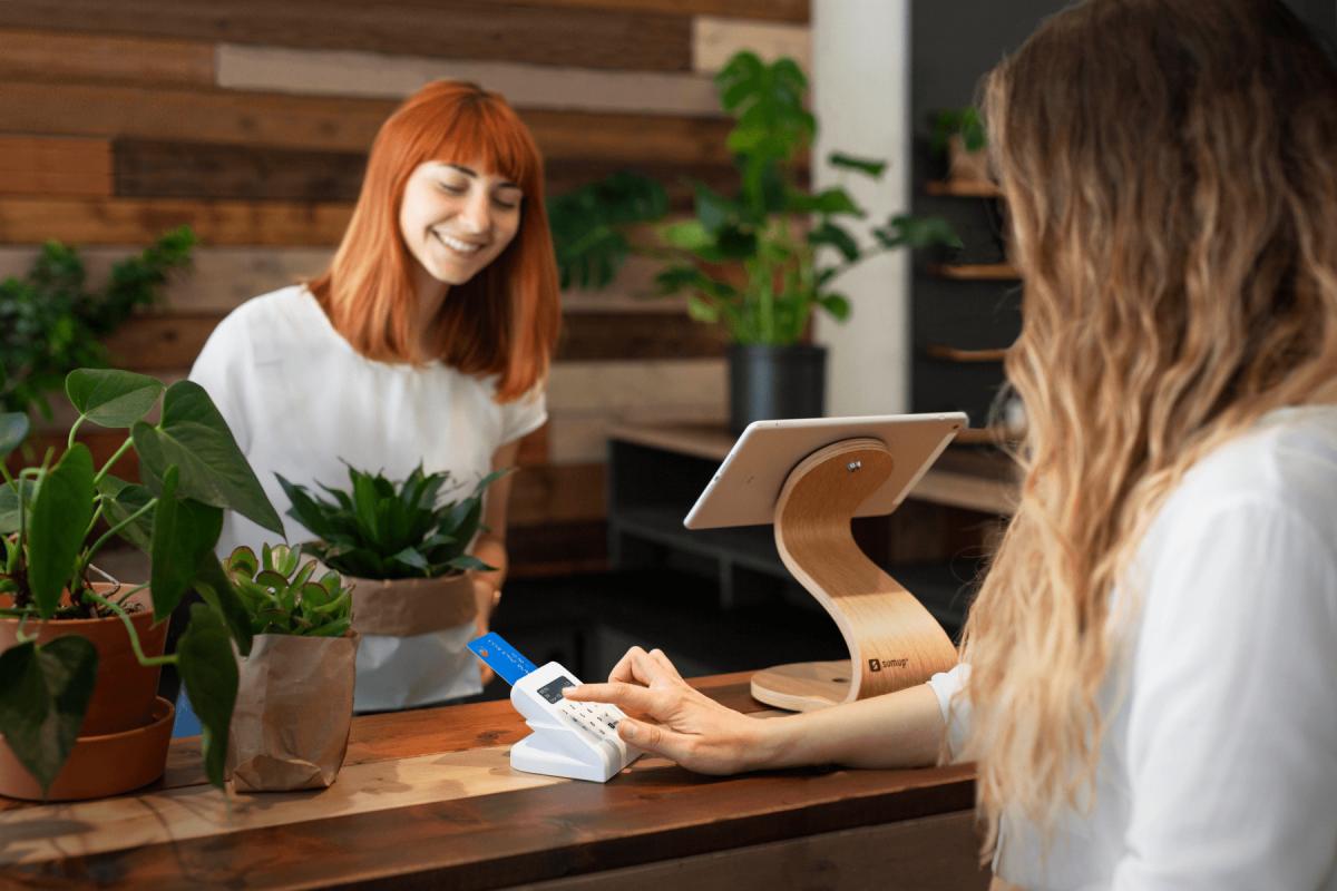 Kundin bezahlt mit einem SumUp Air Kartenterminal KassenSichV-konform