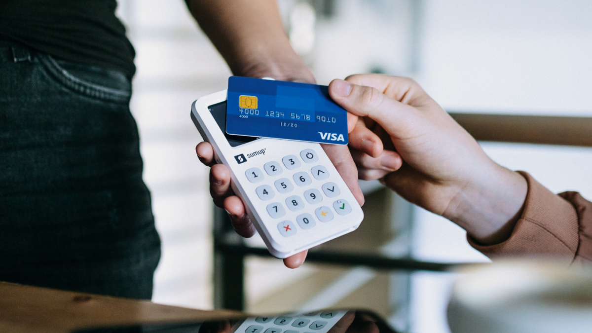 man pays contactless with visa card via sumup 3g card reader in cafe
