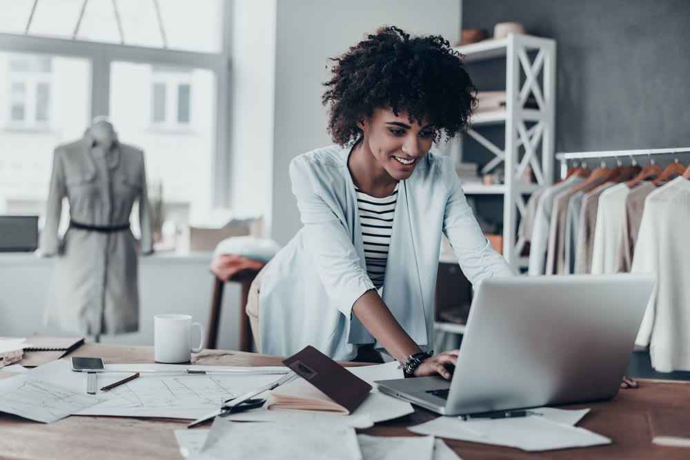 happy black woman business owner working on computer.