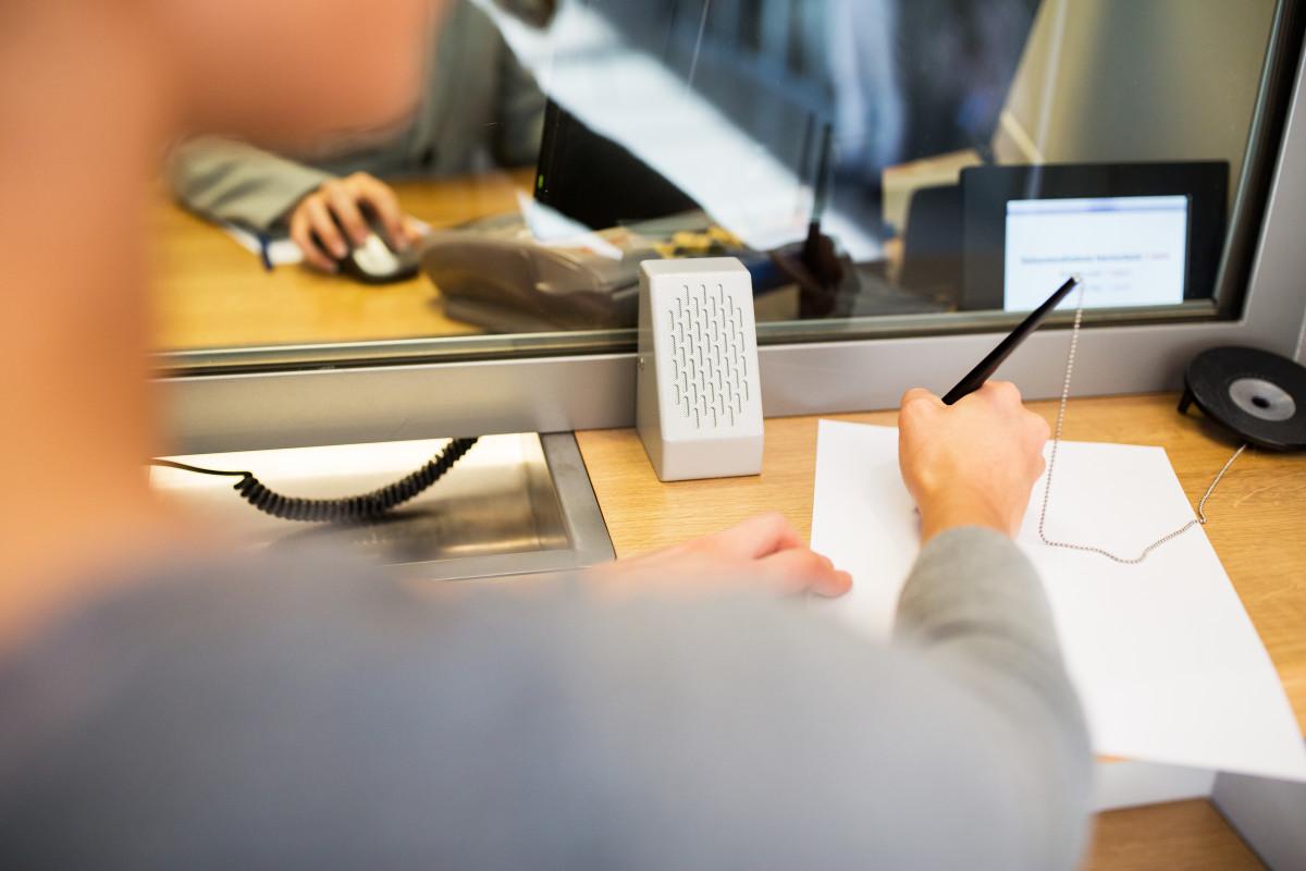 donna in banca compila moduli con penna