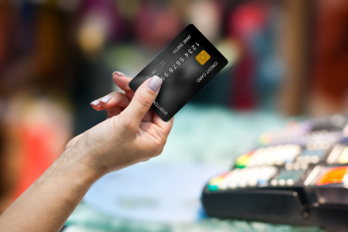 Woman's hand holding a black EMV chip credit card.