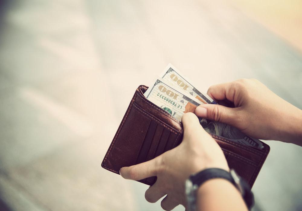 Wallet filled with hundred dollar bills