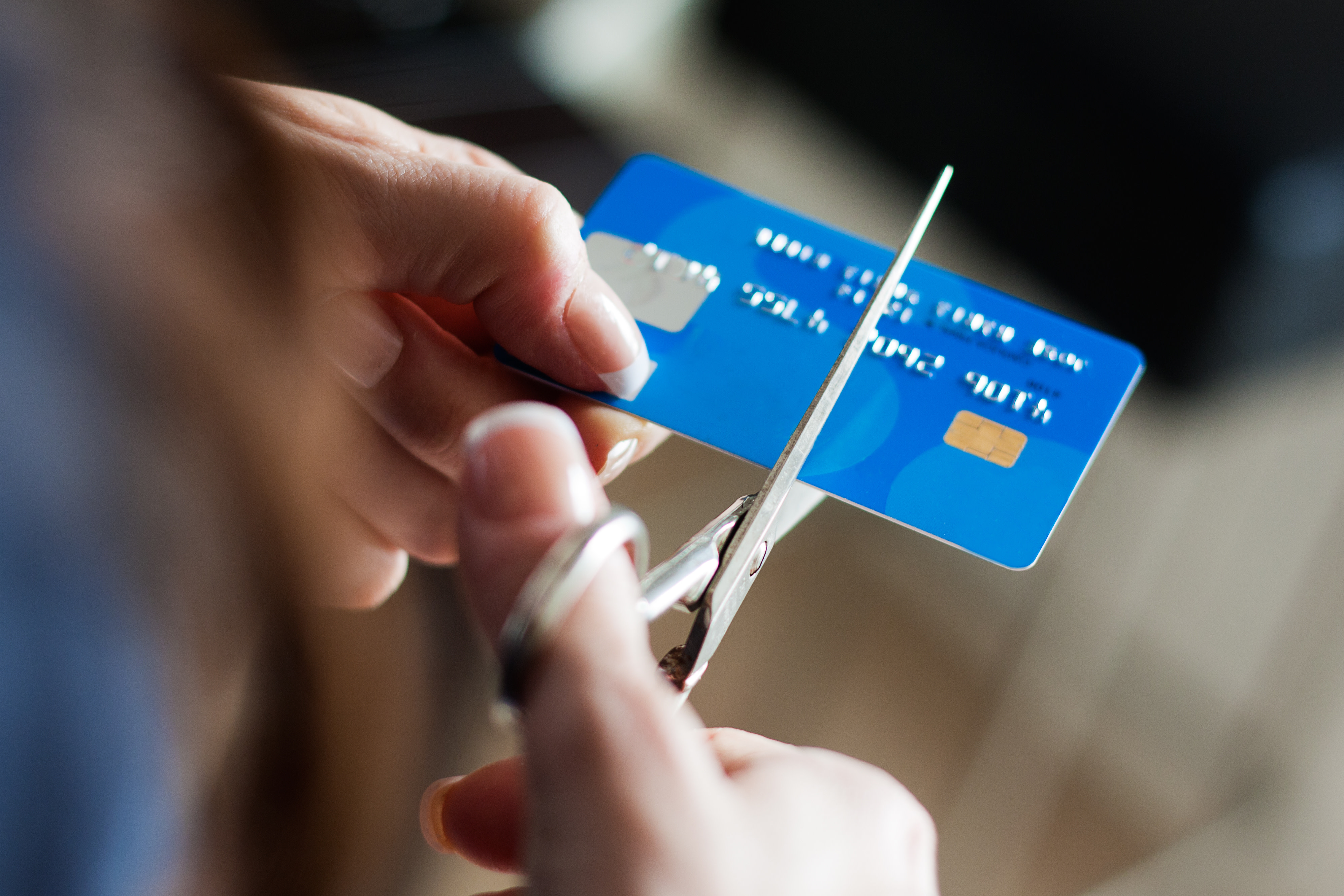 Person cutting a credit card with scissors
