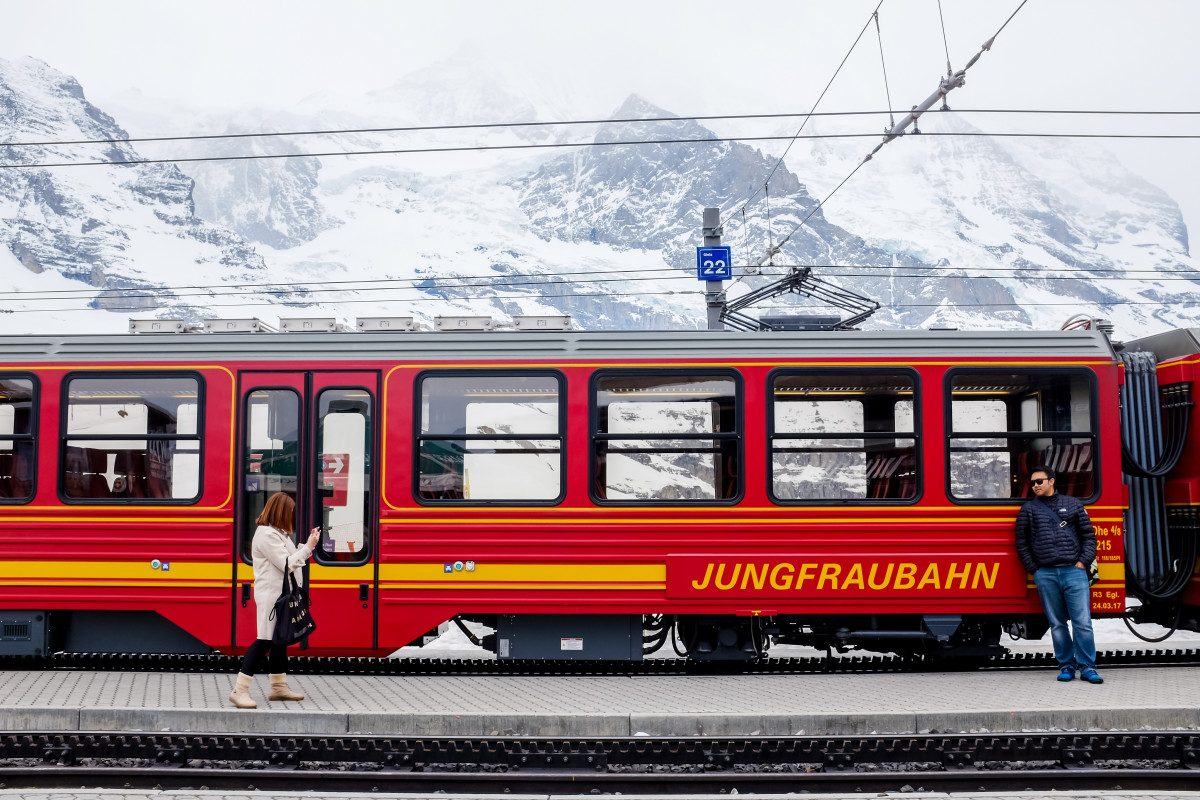The Jungfraubahn waits at a platform as a woman walks by and a man leans against the train.