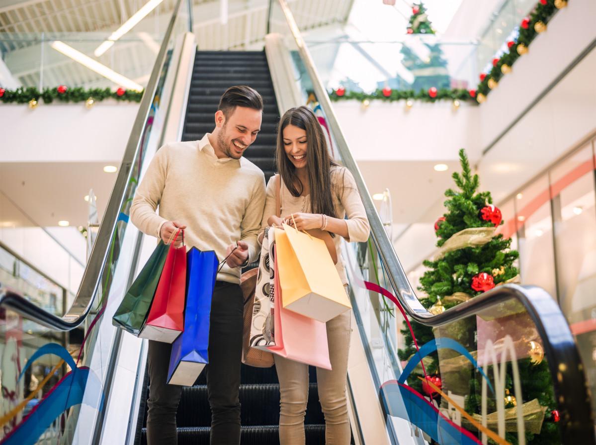 coppia che fa shopping con regali nelle scale mobili