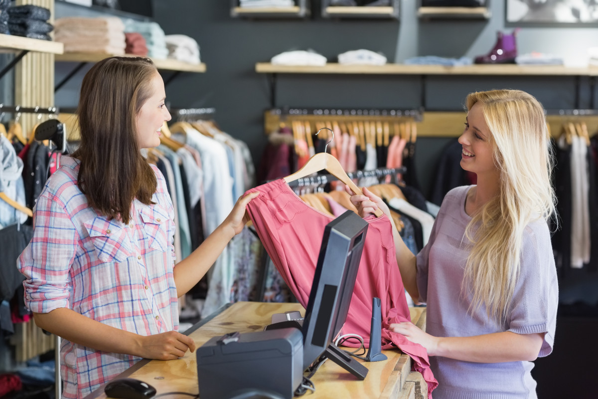 retail worker at the checkout cross-selling to a customer