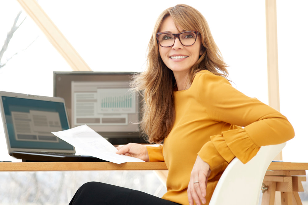 Successful smiling mature businesswoman using laptop and computer