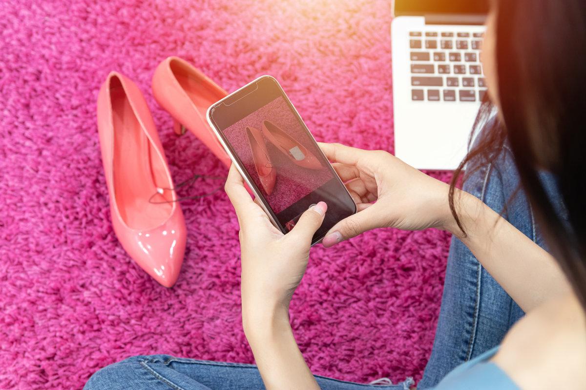Una donna seduta su un tappeto magenta scatta una foto di un paio di scarpe rosa chiaro con i tacchi usando uno smartphone nero.