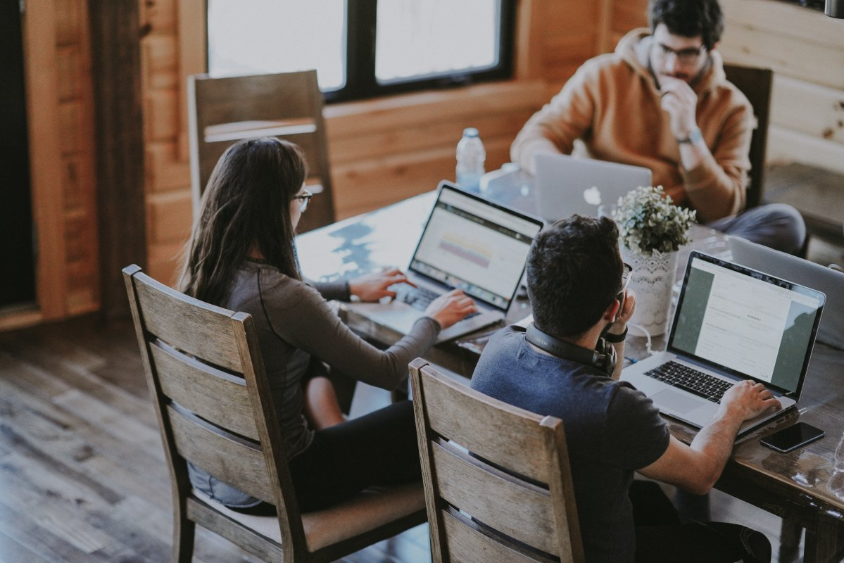Freelancers write invoices on their laptops