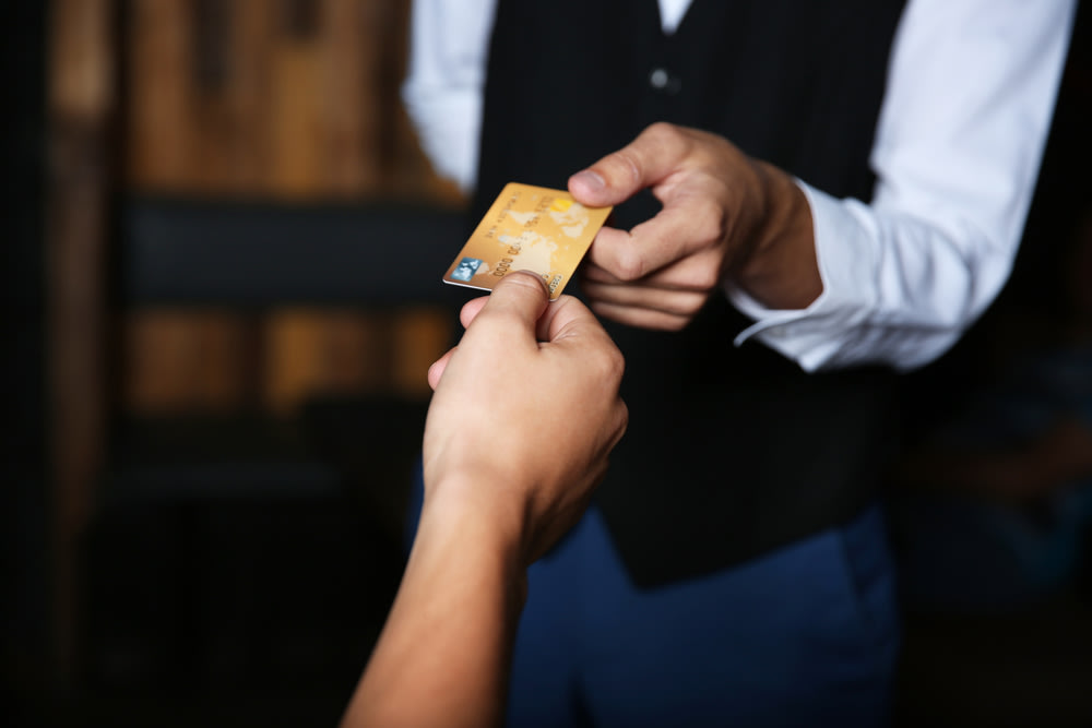 Waiter taking card for tipping.