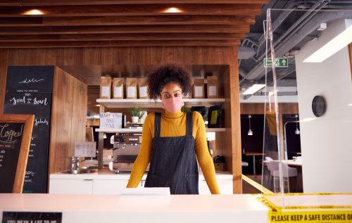Waitress wearing a mask inside a cafe