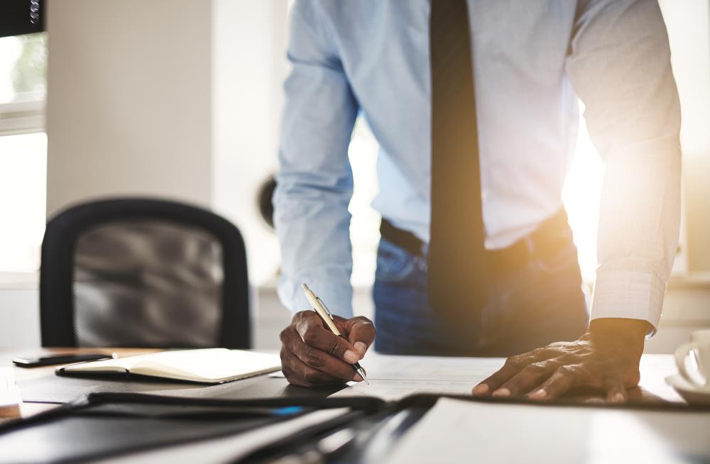 Business owner signing paperwork on desk