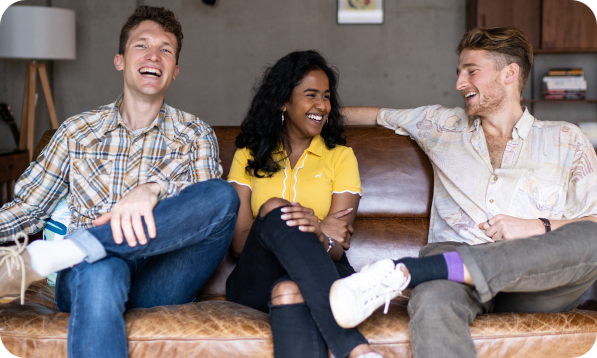 Photo of SumUp employees sitting on a couch laughing – company culture