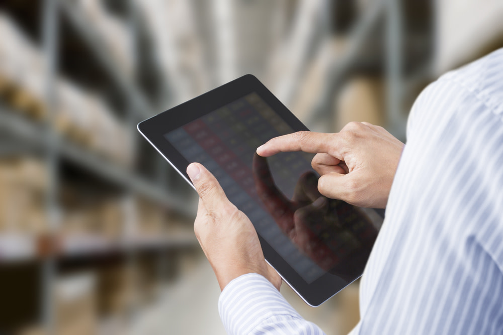 Warehouse worker tracking inventory on a tablet