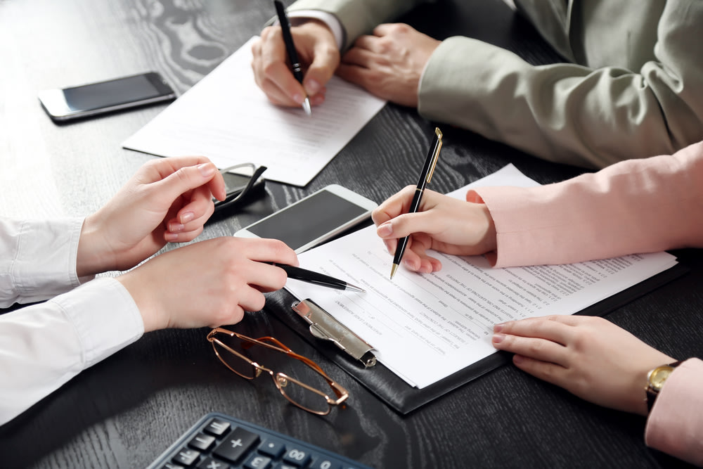 three people signing paperwork on a desk