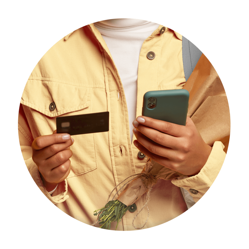 Image of a person holding a banking card in one hand and a smartphone in the other hand