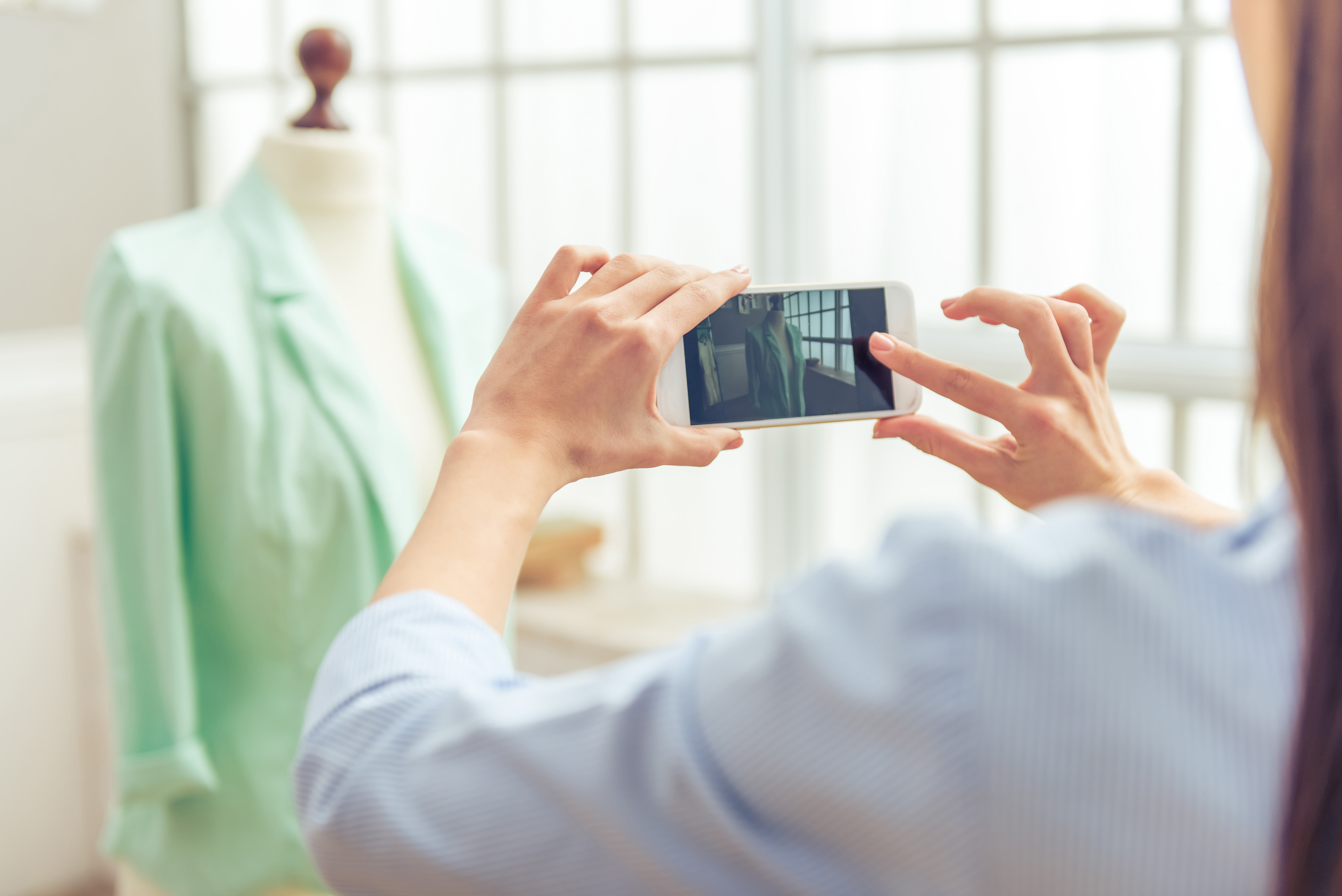 A woman taking a picture of a green blazer