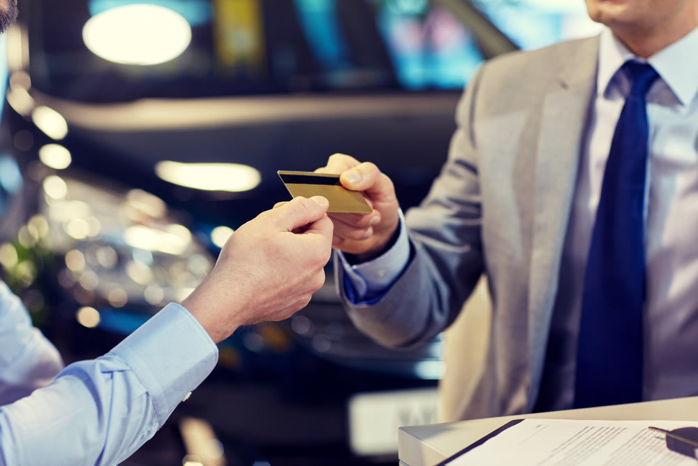 close up of customer giving credit card to car dealer