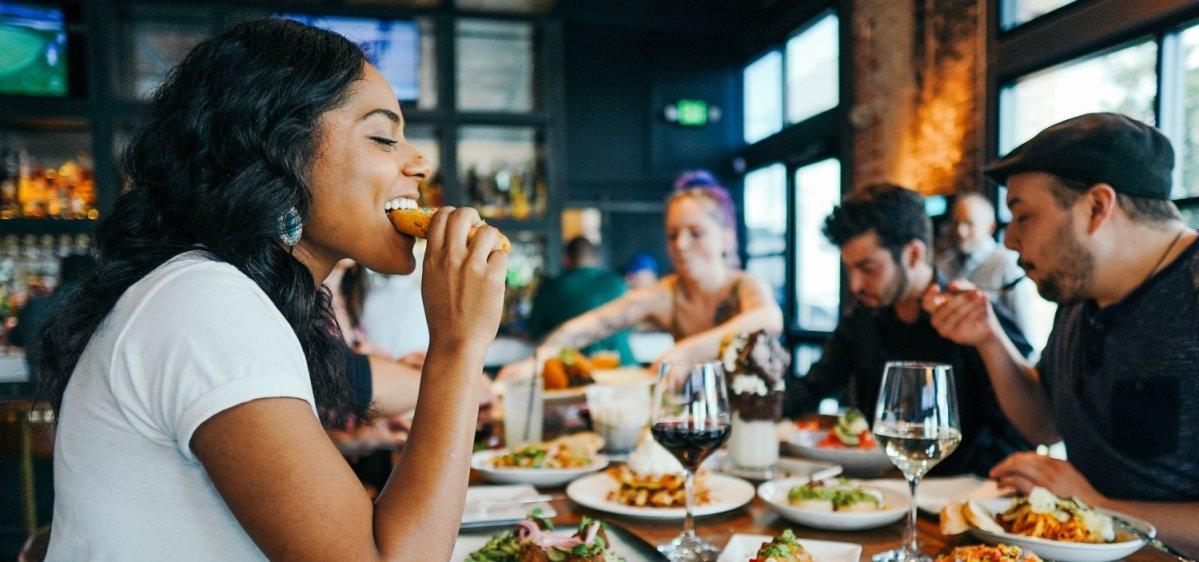 Frau isst mit Freunden im Restaurant